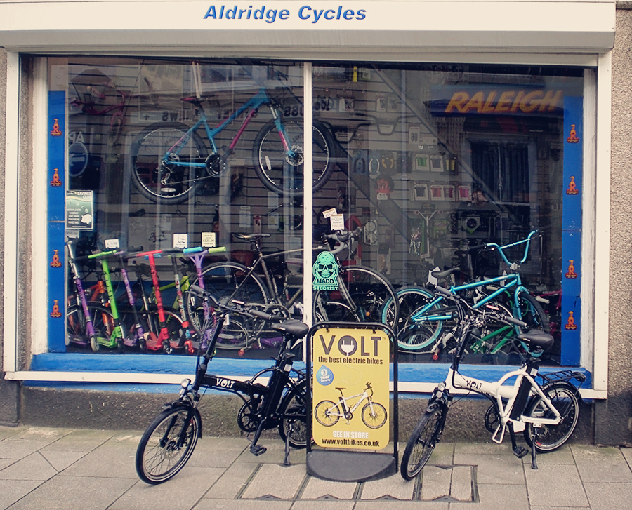 Aldridge Cycles shop with Volt Metro e-bikes and road sign
