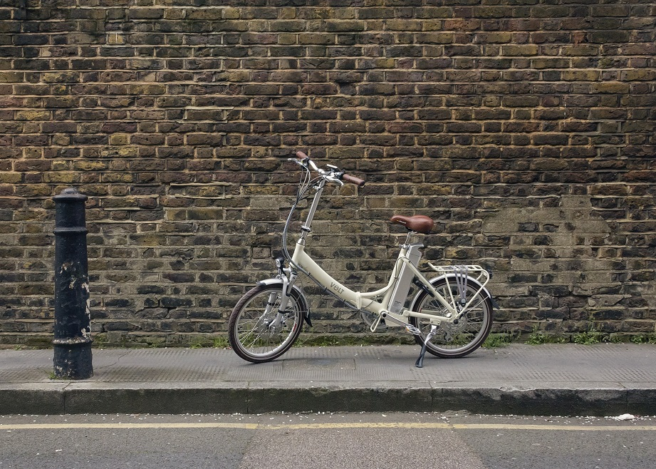 Cream VOLT Metro LS e-bike against a brick wall