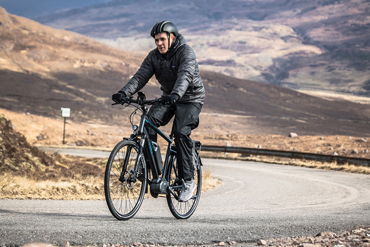 man climbing hill in Applecross with VOLT™ Infinity Shimano step e-bike